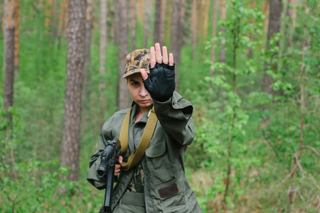 A woman soldier with a weapon shows a hand stop. Stock Photo