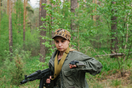 Woman soldier with arms and knife in the woods Stock Photo