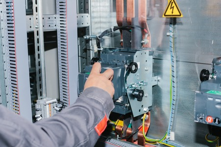 Electrician specialist checking low-voltage cabinet equipment Standard-Bild