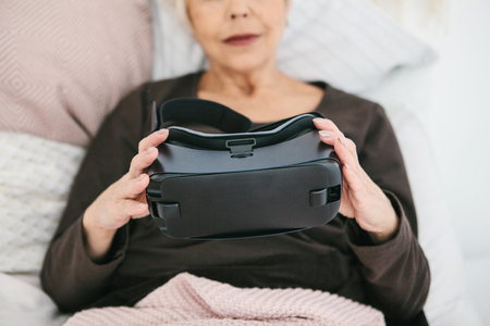 An elderly woman is going to put on virtual reality glasses to use them to immerse in the virtual world. The older generation and new technologies. 免版税图像