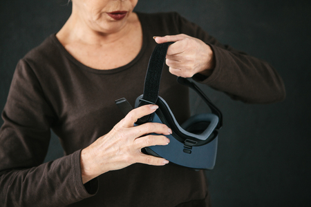 An elderly woman is going to put on virtual reality glasses to use them to immerse in the virtual world. The older generation and new technologies. 写真素材