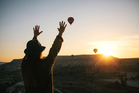 A tourist girl in a hat admires hot air balloons flying in the sky over Cappadocia in Turkey. Impressive sight. Reklamní fotografie
