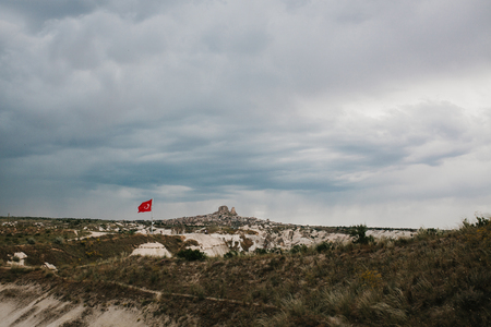Beautiful view of the hills of Cappadocia in Turkey against the backdrop of a dramatic evening sky. They are one of the main natural attractions of these places. Turkish flag on the hill.