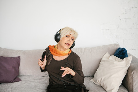 A positive elderly woman listens to music and sings. The older generation and new technologies. Stock Photo