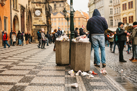 Prague, December 24, 2017: A crowded trash can on Pragues main square during the christmas holidays. A lot of people in the square. Pollution of city streets with trash on holidays. Éditoriale
