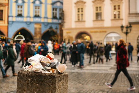 A crowded trash can on Pragues main square during the Christmas break. Many people are blurry in the background. Pollution of city streets with trash on holidays.