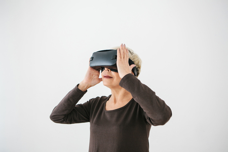 An elderly woman in virtual reality glasses. An elderly person using modern technology.