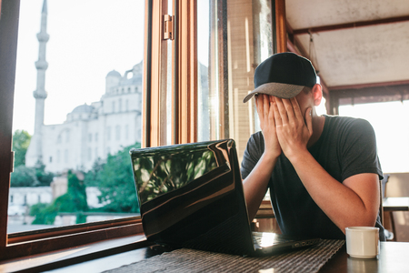 Man in cafe sits at table with computer near window and hidden face by hands.