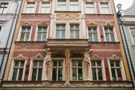 European architecture. Close-up - sculptures - columns in the form of antique characters supporting balcony - facade of vintage historic building.