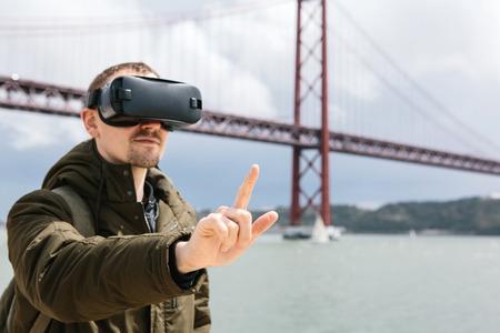 Un hombre usa gafas de realidad virtual. Puente 25 de abril en Lisboa al fondo. El concepto de viaje virtual. El concepto de tecnologías modernas y su uso en la vida cotidiana. Foto de archivo