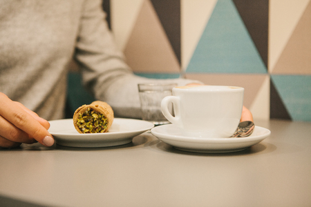 Italian sweet traditional food Cannoli. Fresh pastry with pistachio filling inside. Nearby is a cup of coffee. A girl drinks coffee and eats dessert 版權商用圖片