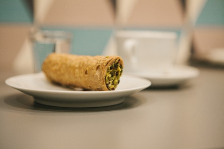 Italian sweet traditional food Cannoli. Fresh pastry with pistachio filling inside