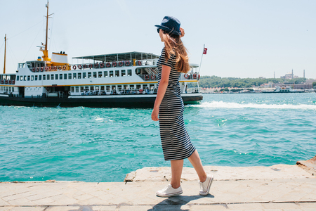 A young beautiful girl in a hat is enjoying a holiday in Turkey and beautiful views of the Bosphorus and Istanbul in the distance. A ship or a passenger boat floats on the water in the background