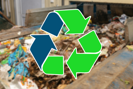 Sign recycling waste. The waste sorting and processing plant is blurry in the background