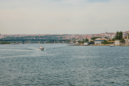 A speed boat sails along the Bosphorus in Istanbul. Urban architecture in the background Stock Photo