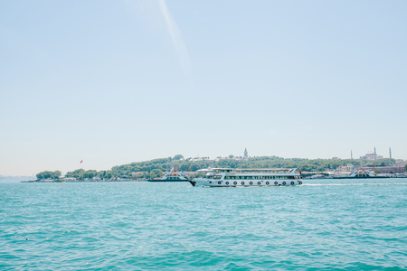 A ship or a passenger liner sails along the Bosphorus in Istanbul. Urban architecture in the background