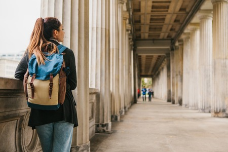 A young girl traveler or tourist or student with a backpack travels to Berdlin in Germany