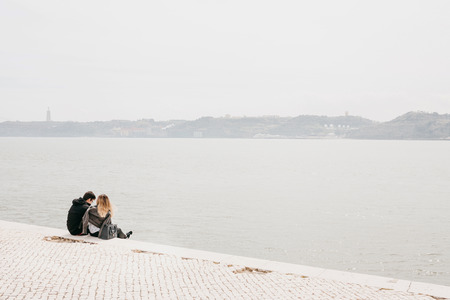 A young couple sitting on the promenade in Belem district in Lisbon in Portugal communicates and enjoys a beautiful view of the city
