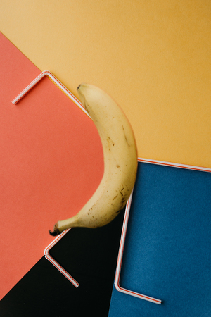 A creative photograph with a banana and small tubes on a bright background