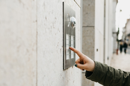 Close up the female hand presses the doorphone button. The girl is calling the intercom