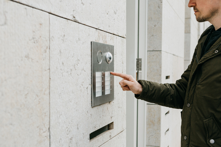 A male local resident or tourist clicks on the doorphone button or calls the intercom. Arrival and call from street to room Stockfoto