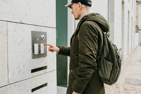 A male local resident or tourist clicks on the doorphone button or calls the intercom. Arrival and call from street to room Stock Photo