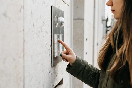 La fille appuie sur le bouton de l'interphone ou appelle l'interphone Banque d'images