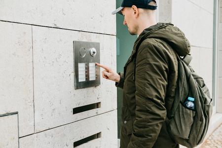 Un residente local o un turista masculino hace clic en el botón del interfono o llama al intercomunicador. Llegada y llamada de calle a habitación.