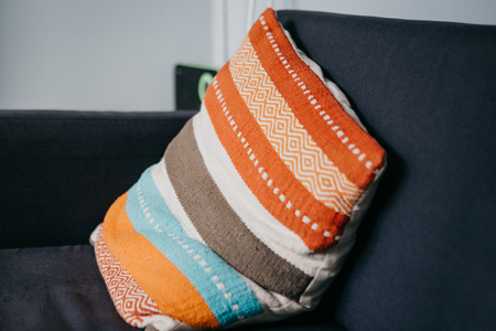 A multicolored pillow lies on the couch in the living room. Cozy atmosphere.