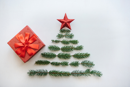 Creative idea for Christmas or New Year theme. A creative Christmas or New Year tree made of fir branches and a star on top. There is a gift to the red box next to it.