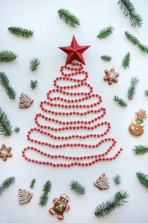 Creative idea for Christmas or New Year theme. A Christmas tree made of beads and a star on top. Next to it lie the traditional gingerbread and spruce branches for decoration.