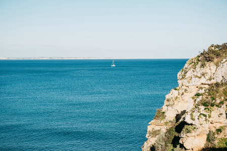 View of the Atlantic Ocean off the coast of Portugal and the sailboat floating in the distance. It is minimalistic. Фото со стока