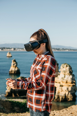 The girl in glasses of a virtual reality. Modern technology in everyday life. 스톡 콘텐츠