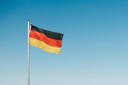 German flag developing in the wind against the blue sky. 版權商用圖片
