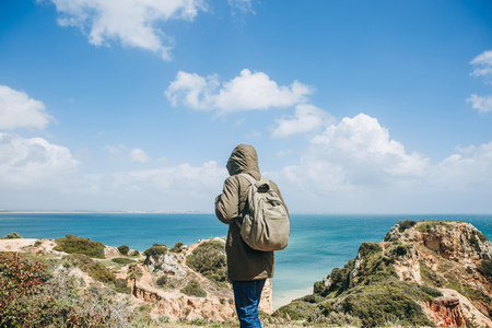 A young hiker with a backpack walks along the Atlantic coast in Portugal. Travel and tourism. Foto de archivo