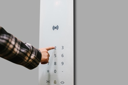Close-up of a girl pressing a touch button in a modern elevator.