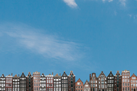 Traditional houses in Amsterdam in the Netherlands in a row against the blue sky.