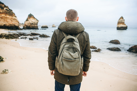 A tourist or traveler with a backpack walks along the coast of the Atlantic Ocean and admires the beautiful view of the ocean near the city called Lagos in Portugal.