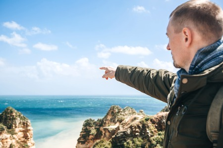 Young man tourist with a backpack enjoying beautiful views of the Atlantic Ocean and the landscape off the coast in Portugal shows a hand to the distance. Stockfoto