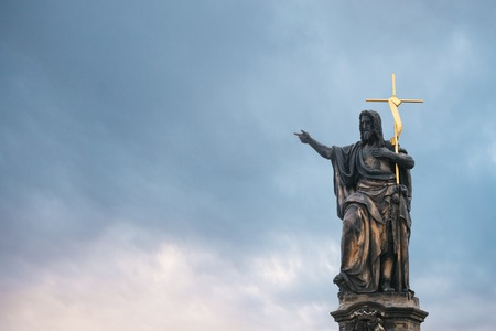Sculpture of St. John the Baptist against the evening sunset sky. One of the ancient statues on the Charles Bridge in Prague in the Czech Republic. European old architecture.