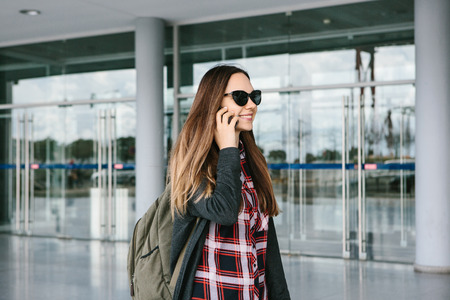 Young beautiful tourist girl at the airport or near the shopping center or the station calls a taxi or talking on a cell phone or talking to friends using a mobile phone. 版權商用圖片
