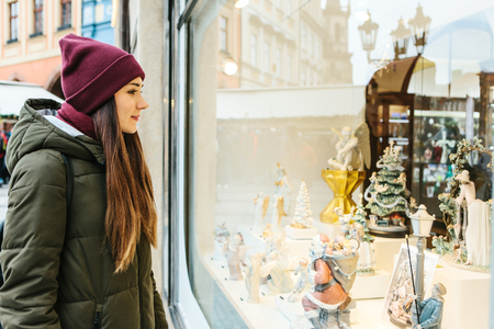 A young beautiful woman or girl looks at the shop window and chooses a Christmas gift. Stock Photo