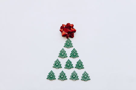 Creative idea in minimalistic style for Christmas or New Year themes. Christmas tree from other small wooden Christmas trees. Celebratory concept.