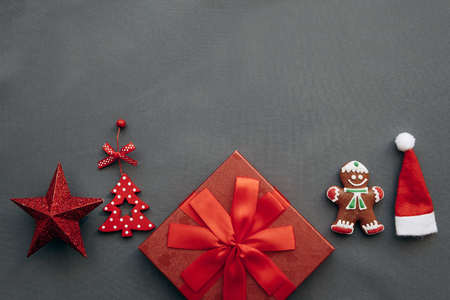 A festive red box with a bow and next to it a variety of Christmas decorations, toys and food including gingerbread on a gray background. Preparation for Christmas and New Year. Imagens