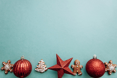 Christmas concept. Christmas balls and gingerbread cookies on a green background. Stock Photo