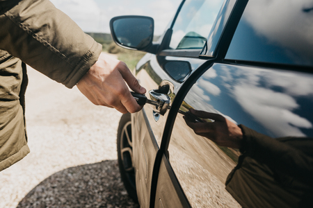 Close-up of a mans hand opens the car door with a key.