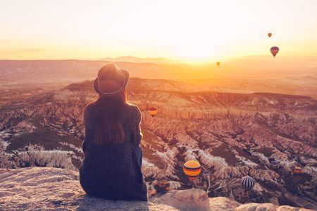 A girl in a hat on top of a hill in silence and loneliness admires the calm natural landscape and balloons.