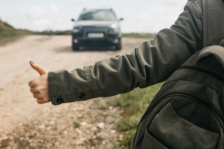 Close-up of a tourist girl with a backpack hitch-hiking. She raised her finger up and tried to stop the car to continue her journey.