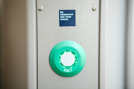 Close-up. Stop button in the train. The inscription in German language is translated - STOP. Above the inscription is translated - Continue to press the button.
