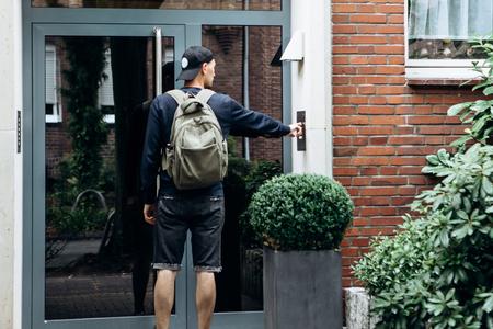 Der Tourist klingelt an der Tür, um in das von ihm gebuchte Zimmer einzuchecken, oder der Student mit dem Rucksack kehrt nach dem Unterricht am Institut oder im Urlaub nach Hause zurück. Standard-Bild